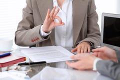 Groupe de gens d'affaires ou d'avocats lors de la réunion discutant des papiers de contrat Femme affichant le signe en bon état Photo stock