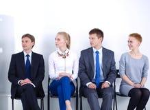 Groupe de gens d'affaires s'asseyant sur la chaise dans le bureau Groupe de gens d'affaires Photos stock