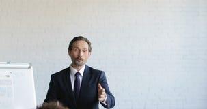 Groupe de gens d'affaires sur la présentation dans le cours de formation de Hall Listening To Successful Businessman de conférenc banque de vidéos