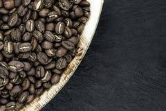 Groupe de grains de café dans le plat naturel de feuille de banane sur la surface en pierre noire de fond image libre de droits