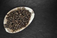 Groupe de grains de café dans le plat naturel de feuille de banane sur la surface en pierre noire de fond photo stock