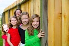 Groupe de Grils dans une rangée souriant dans une barrière en bois Image stock