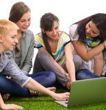 Groupe de jeune étudiant s'asseyant sur l'herbe verte Photos stock