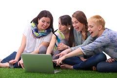 Groupe de jeune étudiant s'asseyant sur l'herbe verte Photos libres de droits