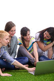 Groupe de jeune étudiant s'asseyant sur l'herbe verte Image stock