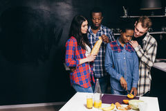 Groupe de jeune cuisinier d'amis à la cuisine bonheur Photographie stock libre de droits