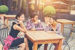 Groupe de jeune hippie s'asseyant dans un café, jeunes amis gais Photographie stock libre de droits