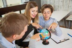 Groupe de jeune recherche de globe d'étude d'étudiants de pays de voyage Image stock