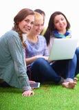 Groupe de jeune étudiant s'asseyant sur l'herbe verte Images libres de droits