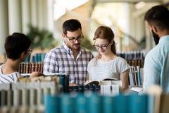 Groupe de jeunes étudiants étudiant ensemble à la bibliothèque Photo stock