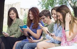 Groupe de jeunes étudiants universitaires heureux regardant des téléphones portables i image stock