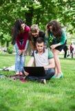 Groupe de jeunes étudiants universitaires s'asseyant sur l'herbe Photographie stock