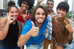 Groupe de jeunes adultes de hippie international montrant le pouce Photographie stock