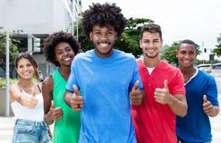 Groupe de jeunes adultes internationaux montrant des pouces dans la ville Photos stock