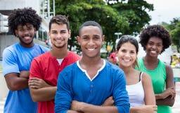 Groupe de jeunes adultes internationaux riant de l'appareil-photo dans la ville Photographie stock libre de droits