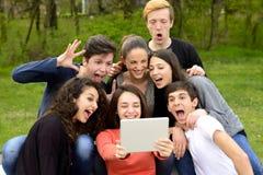 Groupe de jeunes adultes passant en revue un comprimé Photos stock