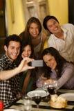 Groupe de jeunes adultes prenant une photo de selfie image stock
