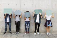 Groupe de jeunes adultes tenant dehors le copyspace vide t de plaquette images stock