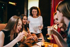 Groupe de jeunes amies prenant le déjeuner dans le restaurant d'aliments de préparation rapide mangeant des hamburgers de métier Image stock
