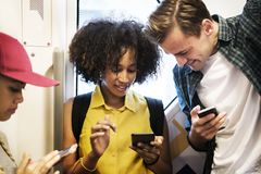 Groupe de jeunes amis adultes à l'aide des smartphones dans le souterrain Photographie stock