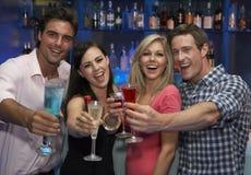 Groupe de jeunes amis appréciant la boisson dans la barre Images libres de droits