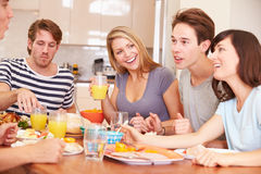 Groupe de jeunes amis appréciant le repas à la maison Photographie stock libre de droits