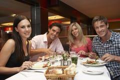 Groupe de jeunes amis appréciant le repas dans le restaurant Photo stock
