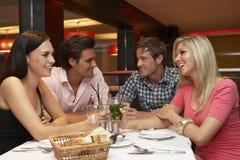 Groupe de jeunes amis appréciant le repas dans le restaurant Image libre de droits