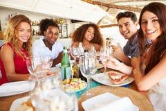 Groupe de jeunes amis appréciant le repas dans le restaurant extérieur Photographie stock