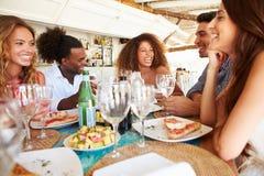 Groupe de jeunes amis appréciant le repas dans le restaurant extérieur Photos libres de droits
