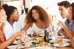 Groupe de jeunes amis appréciant le repas dans le restaurant extérieur Image stock