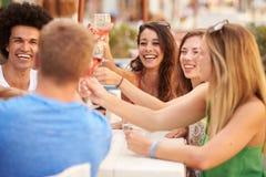 Groupe de jeunes amis appréciant le repas dans le restaurant extérieur Images libres de droits