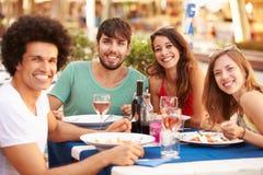 Groupe de jeunes amis appréciant le repas dans le restaurant extérieur Photo libre de droits