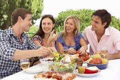 Groupe de jeunes amis appréciant le repas extérieur ensemble Image libre de droits