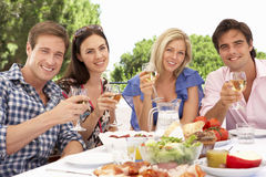 Groupe de jeunes amis appréciant le repas extérieur ensemble Photos libres de droits