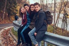 Groupe de jeunes amis avec des sacs à dos se reposant sur la rambarde près de la route avec une belles forêt et rivière à l'arriè image libre de droits