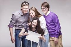 Groupe de jeunes amis avec le panneau d'annonce Photos stock