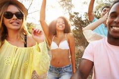 Groupe de jeunes amis ayant la partie sur la plage ensemble Photographie stock libre de droits