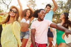 Groupe de jeunes amis ayant la partie sur la plage ensemble Image stock