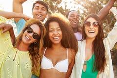 Groupe de jeunes amis ayant la partie sur la plage ensemble Photo stock
