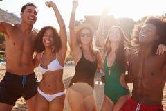 Groupe de jeunes amis ayant la partie sur la plage ensemble Photos stock