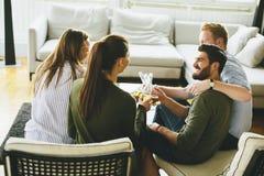 Groupe de jeunes amis buvant du cidre et ayant l'amusement dans la chambre Image stock