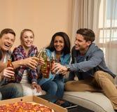 Groupe de jeunes amis célébrant dans l'intérieur à la maison Photos libres de droits