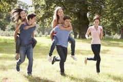 Groupe de jeunes amis courant par la campagne Images stock