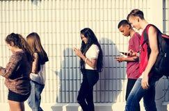 Groupe de jeunes amis d'adolescent marchant à la maison après école utilisant photographie stock libre de droits