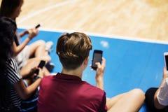 Groupe de jeunes amis d'adolescent sur un terrain de basket détendant et à l'aide du smartphone Image libre de droits