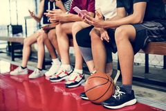 Groupe de jeunes amis d'adolescent sur un terrain de basket détendant utilisant le concept de dépendance de smartphone Photo stock