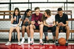 Groupe de jeunes amis d'adolescent sur un terrain de basket détendant utilisant le smartphone Photographie stock libre de droits