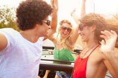Groupe de jeunes amis dansant derrière la voiture à couvercle serti Images libres de droits