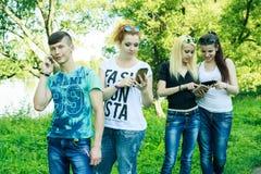 Groupe de jeunes amis de hippie à l'aide du téléphone intelligent avec le désintérêt sur l'un l'autre Photo libre de droits